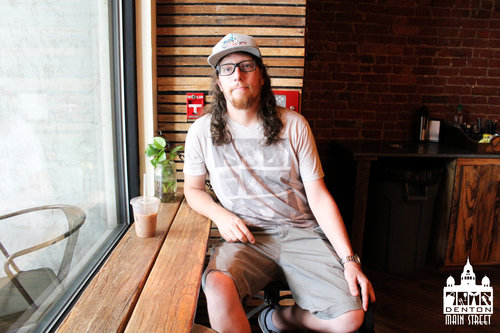 a man sits at a coffee shop window seat with an iced cup of coffee.