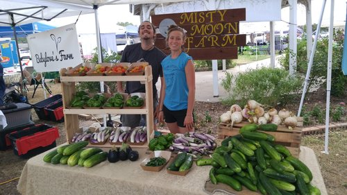 a picture of two people posing around produce at a farmer's market