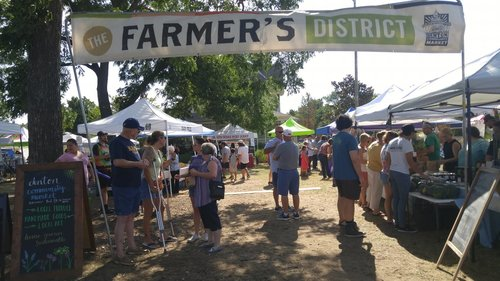 a picture of people milling around shopping at an outdoor farmer's market.