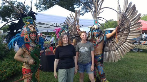 a picture of two people posing with traditional indigenous dancers.