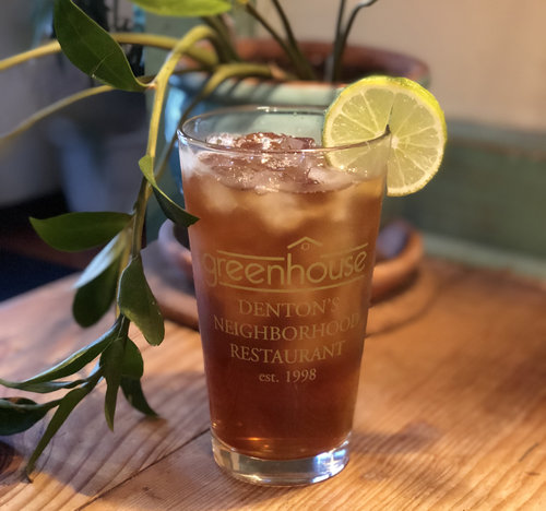 """a glass of iced tea next to a plant on a wooden table.the glass reads """"greenhouse restaurant - denton's neighborhood restaurant est. 1998"""""""