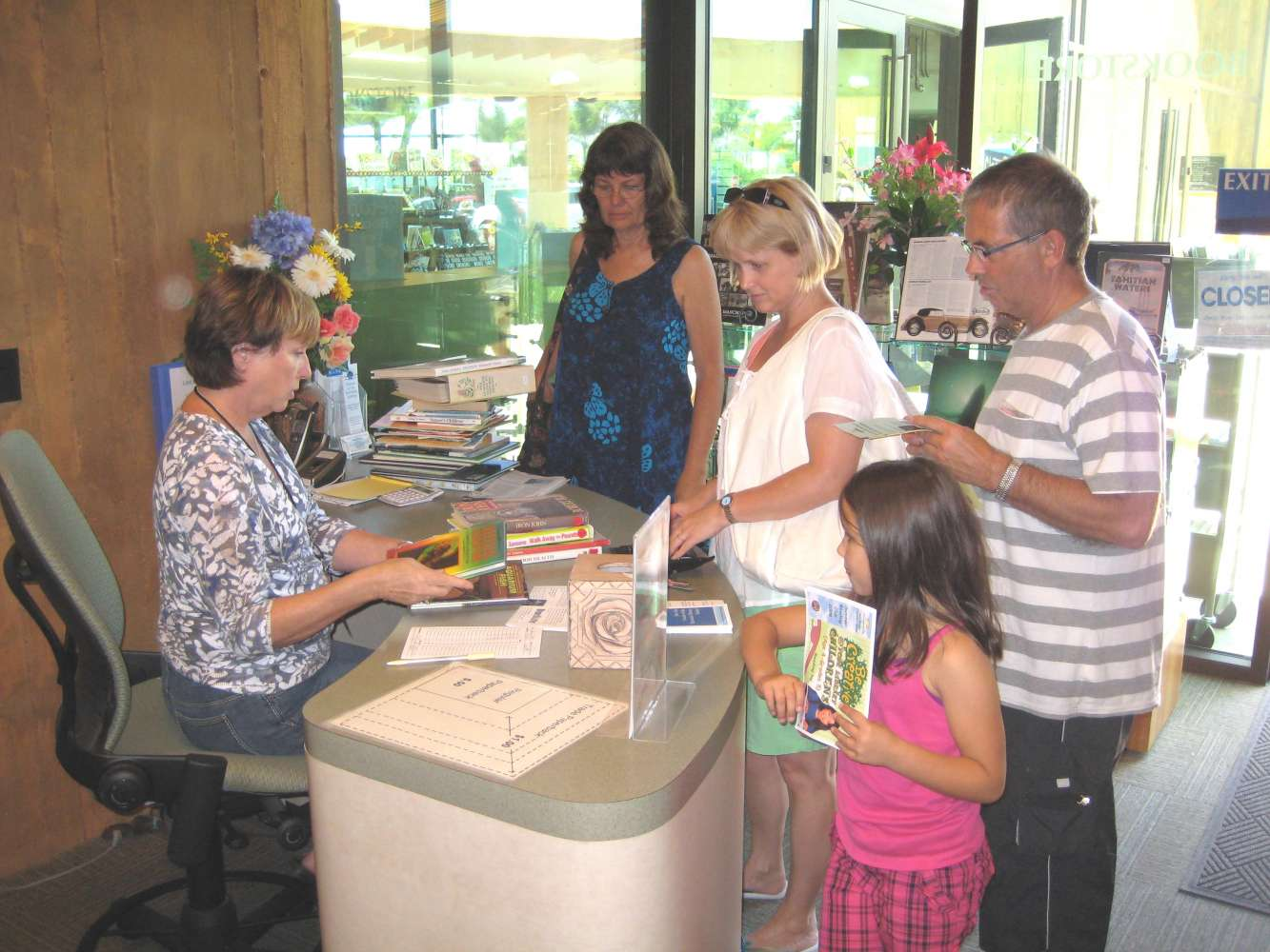 Friends of the Encinitas Library Bookstore cashiers desk with customers waiting to purchase their books.