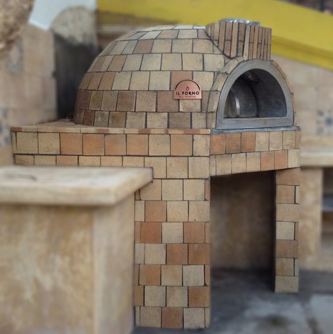 A fixed dome shaped pizza oven with fire bricks finishing. The oven is installed in an kitchen outdoors in a garden.