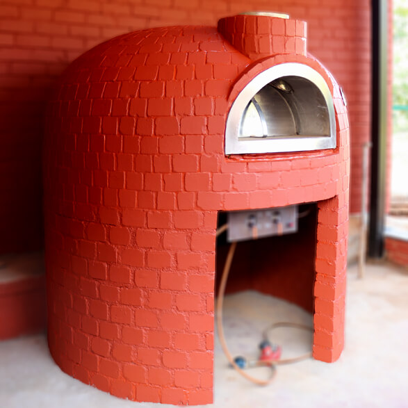Dome shaped pizza oven with red brick finishing. The red bricks are painted with red colour that is matching with the red bricks behind the oven.