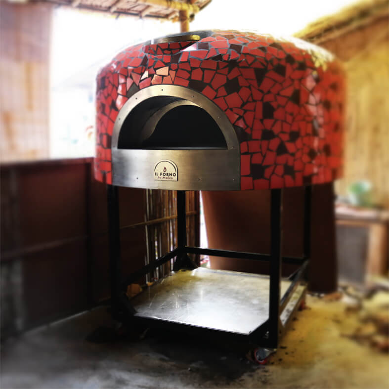 A semi-mobile brick oven on a trolley on wheels. The oven has a broken tile mosaic finishing in red and brown.