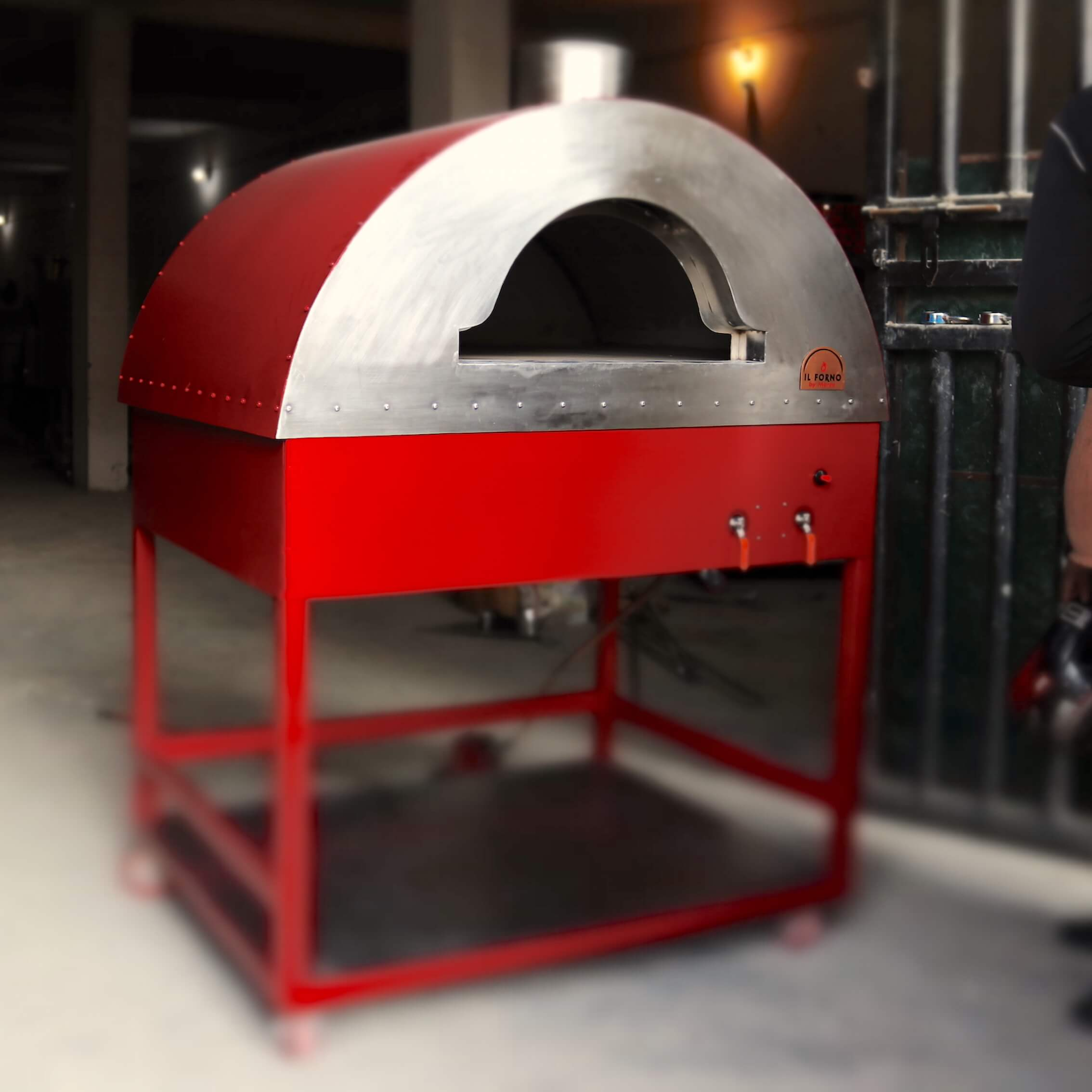 Red mobile oven in metal on wheels. The oven has a gas burner system and a stainless steel shelf underneath for storing of the wood.