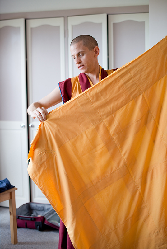 Dornying folds his chögu in his bedroom at the Kadampa Meditation Centre Australia (Monbulk). This robe is worn during teachings to signify wisdom. Dornying is packing his bag for the Heruka Centre, where he will spend the next couple of days.