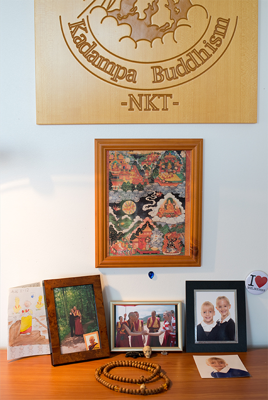 Dornying's bedroom desk features a photograph of he and his mother; his neices; and of a rare opportunity: meeting with the spiritual leader, Geshe Kelsang Gyatso.