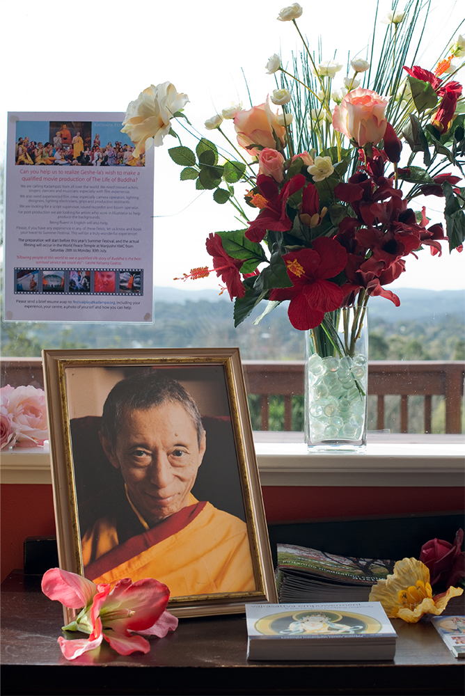 Upon the table in the KMCA foyer rests a photograph of Geshe Kelsang Gyatso, as well as flyers promoting upcoming Buddhist events, both local and international.