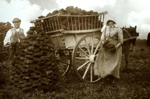 An Irish couple loads turf into their cart (c, 1905)