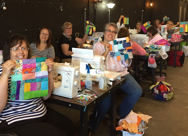 Quilters showing off their improv starter blocks
