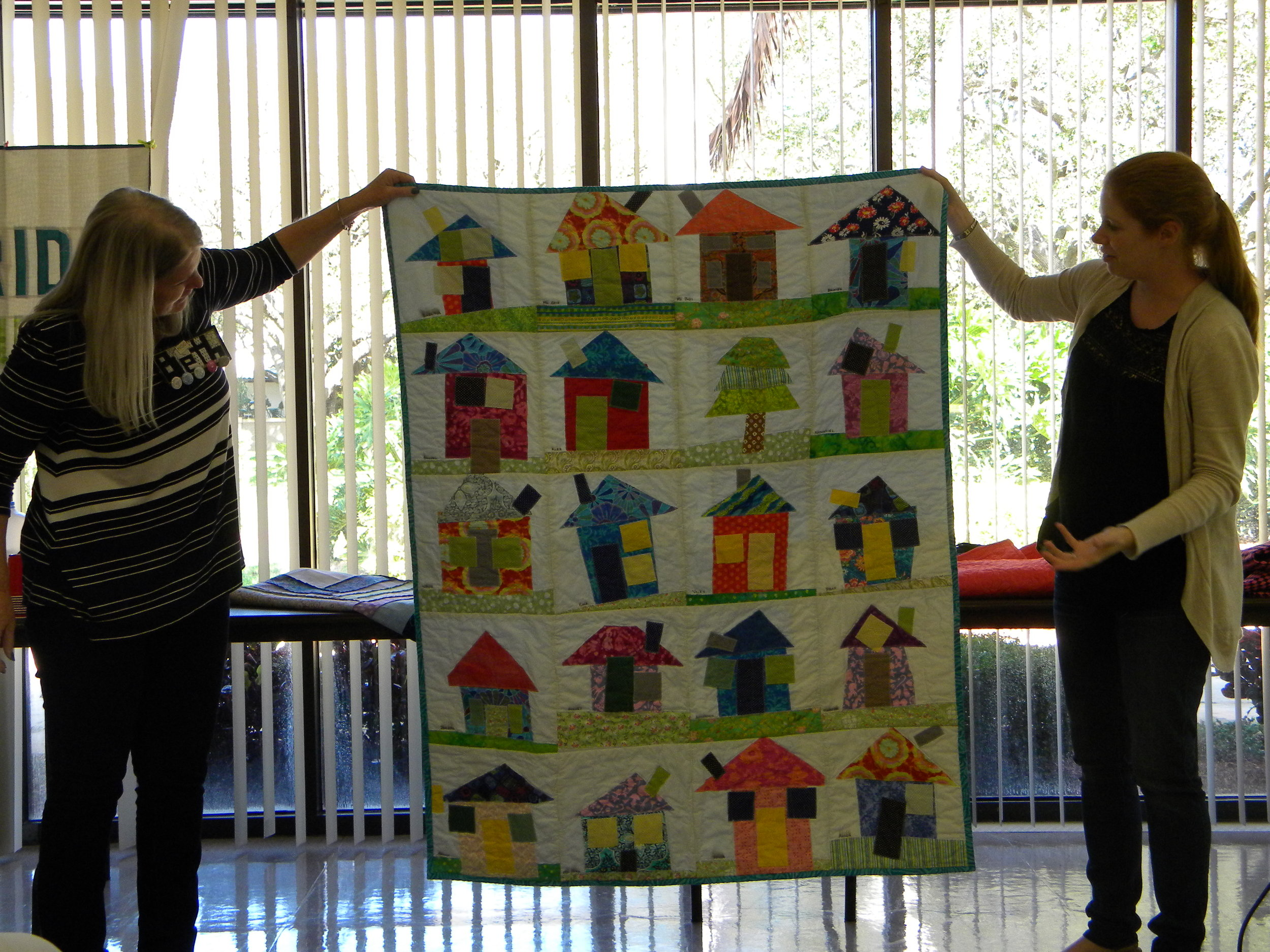 """Nicole, with the finished house quilt. The blocks were """"made"""" by children in a school class."""
