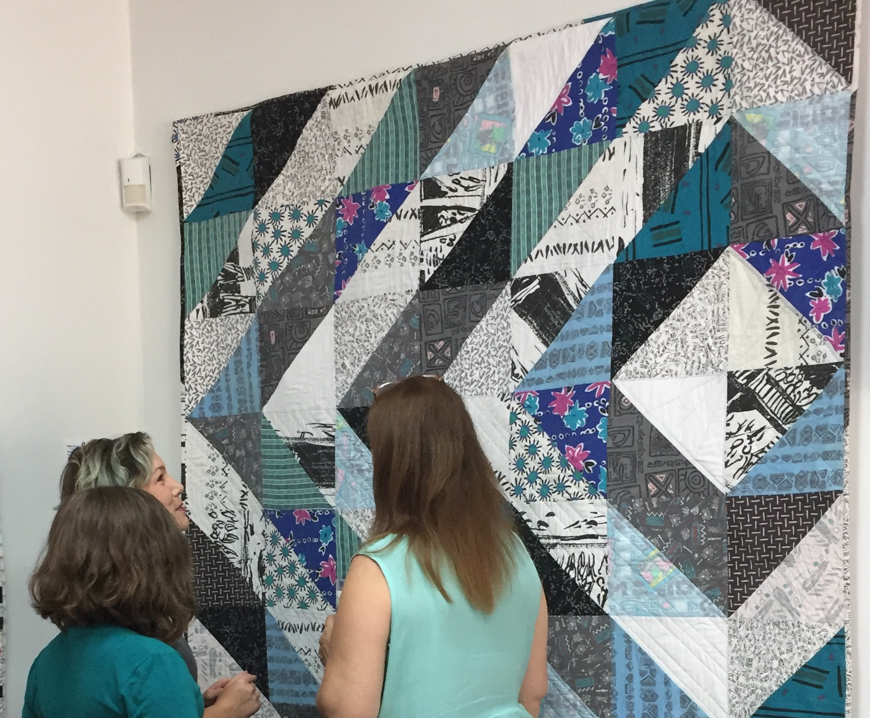 Artist Debby Schindall discussing her quilt with exhibit attendees.