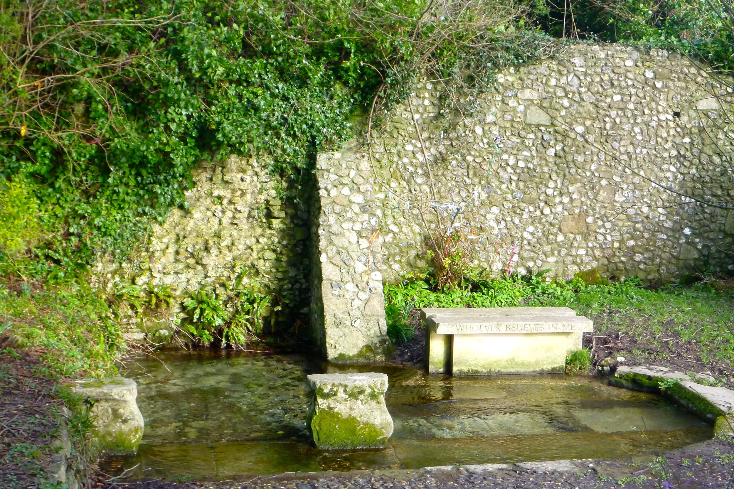 """The bench next to the well has the words """"Whoever Believes in Me"""" carved along it's side. Prayer tree/bush is just behind bench."""