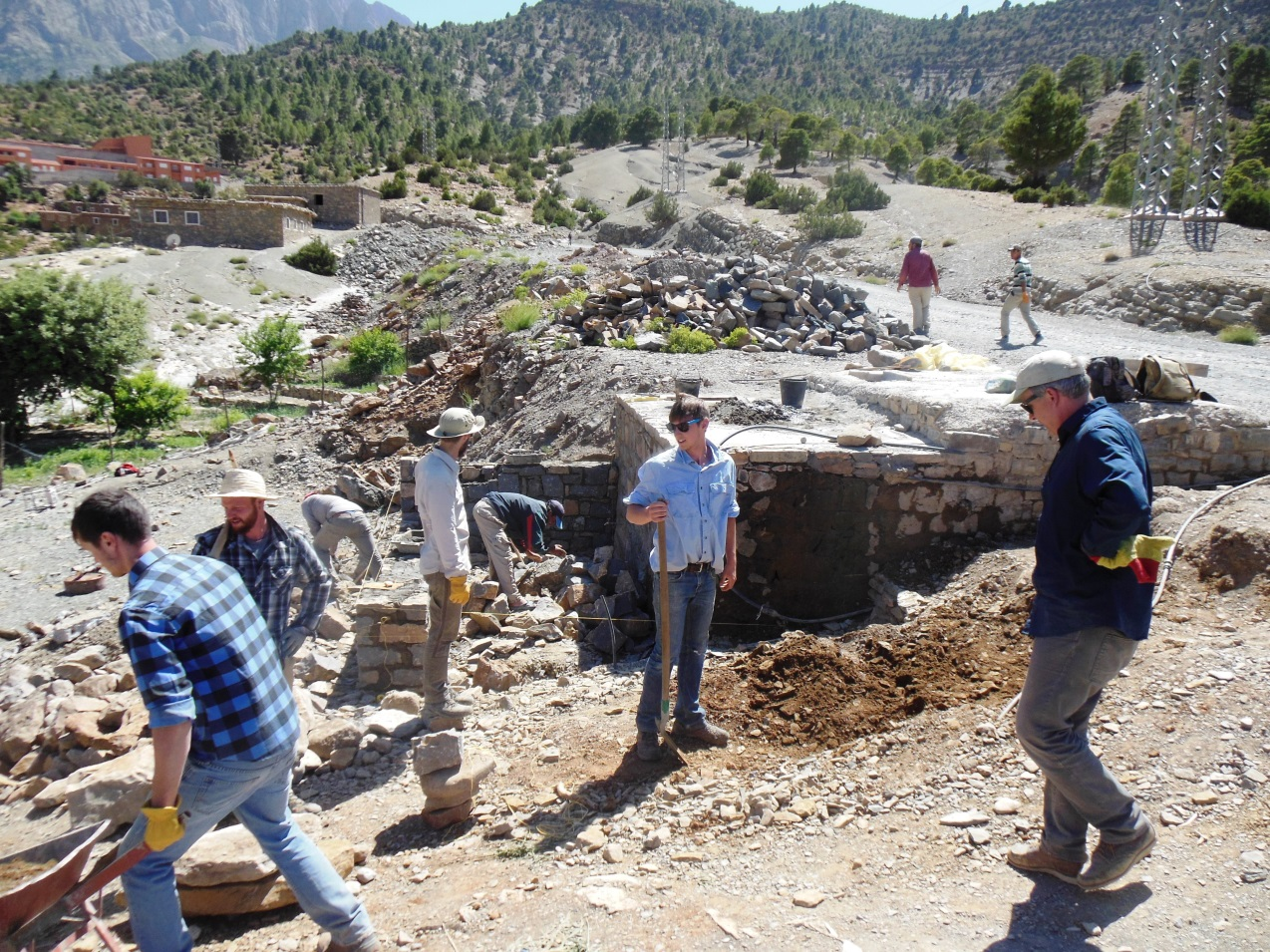 Professor Chris Livingston (right) directing his students in construction of the water fountain at the Amezray water chateau.