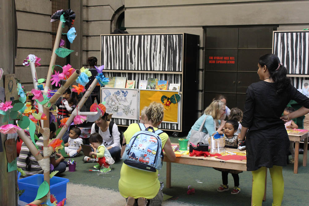 Participants' flowers and leaves fill the cardboard tree, 'Come play in our garden' in Play Pod, State Library Victoria.