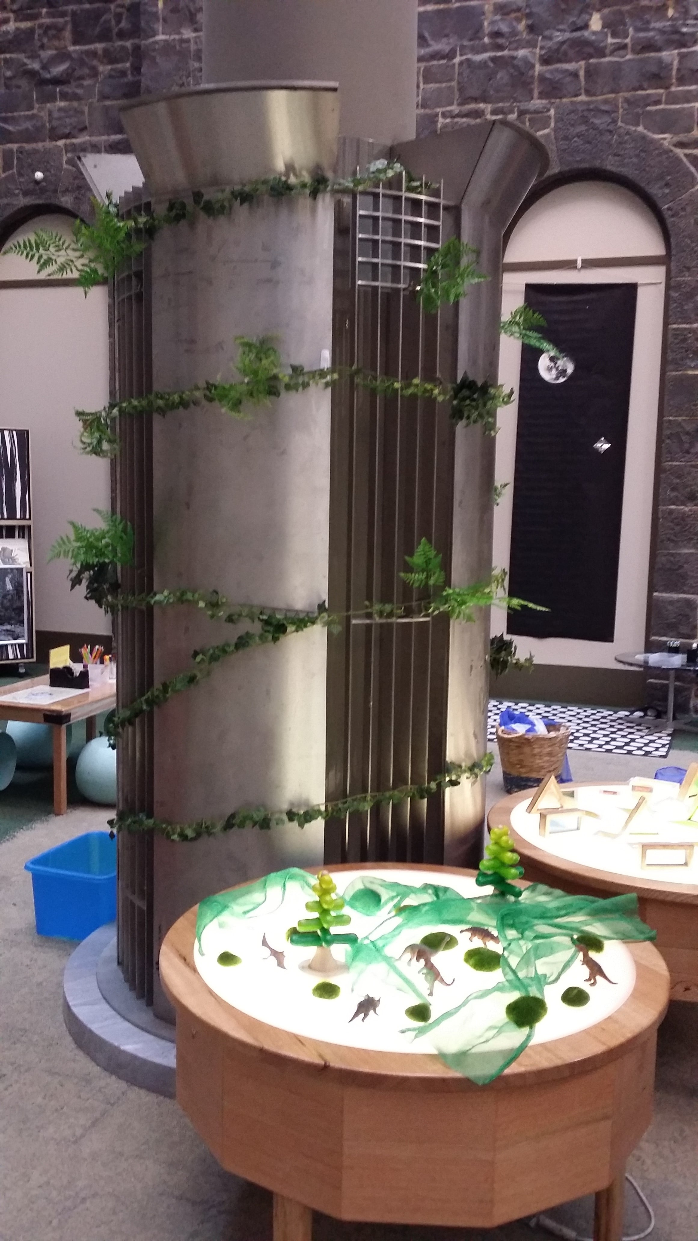 Children are encouraged to add to the forest of vines around the pillar, celebrating their own creative work.