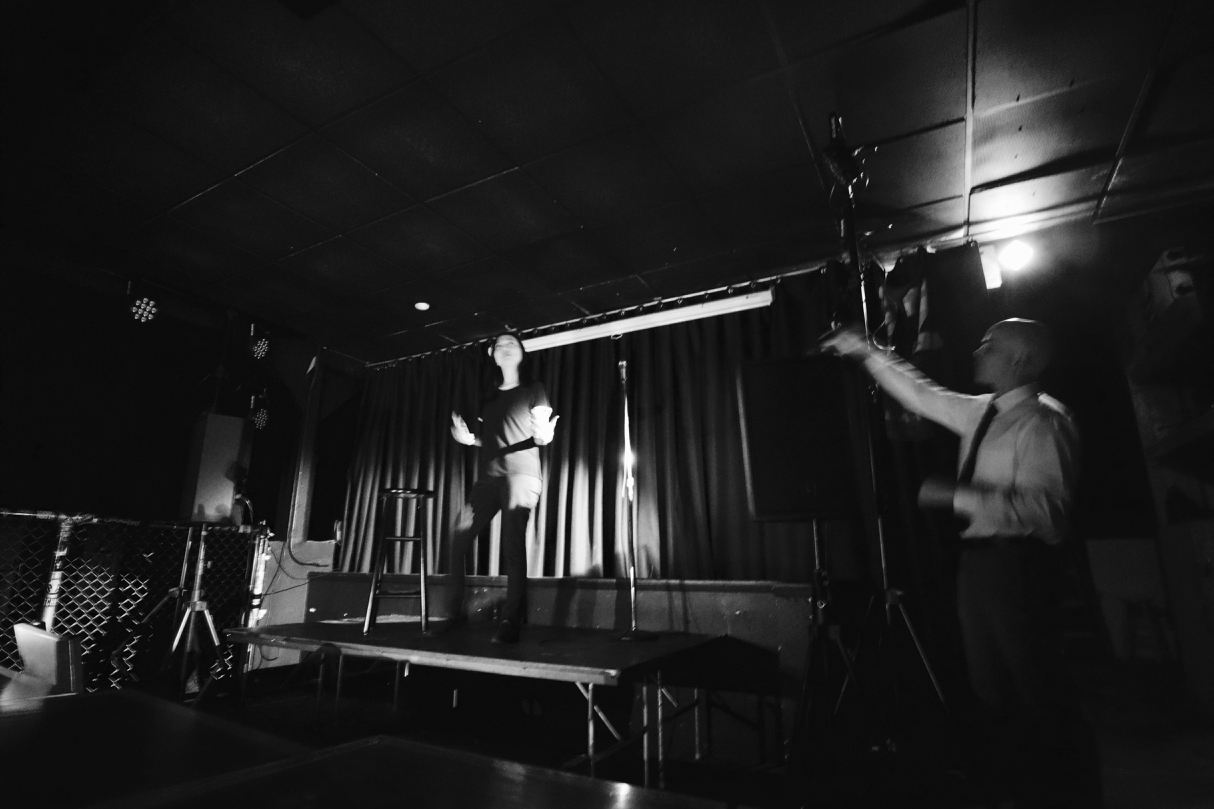 After the lights went out, Kiltoff (R) using a flashlight to light the stage // Garret Hunt