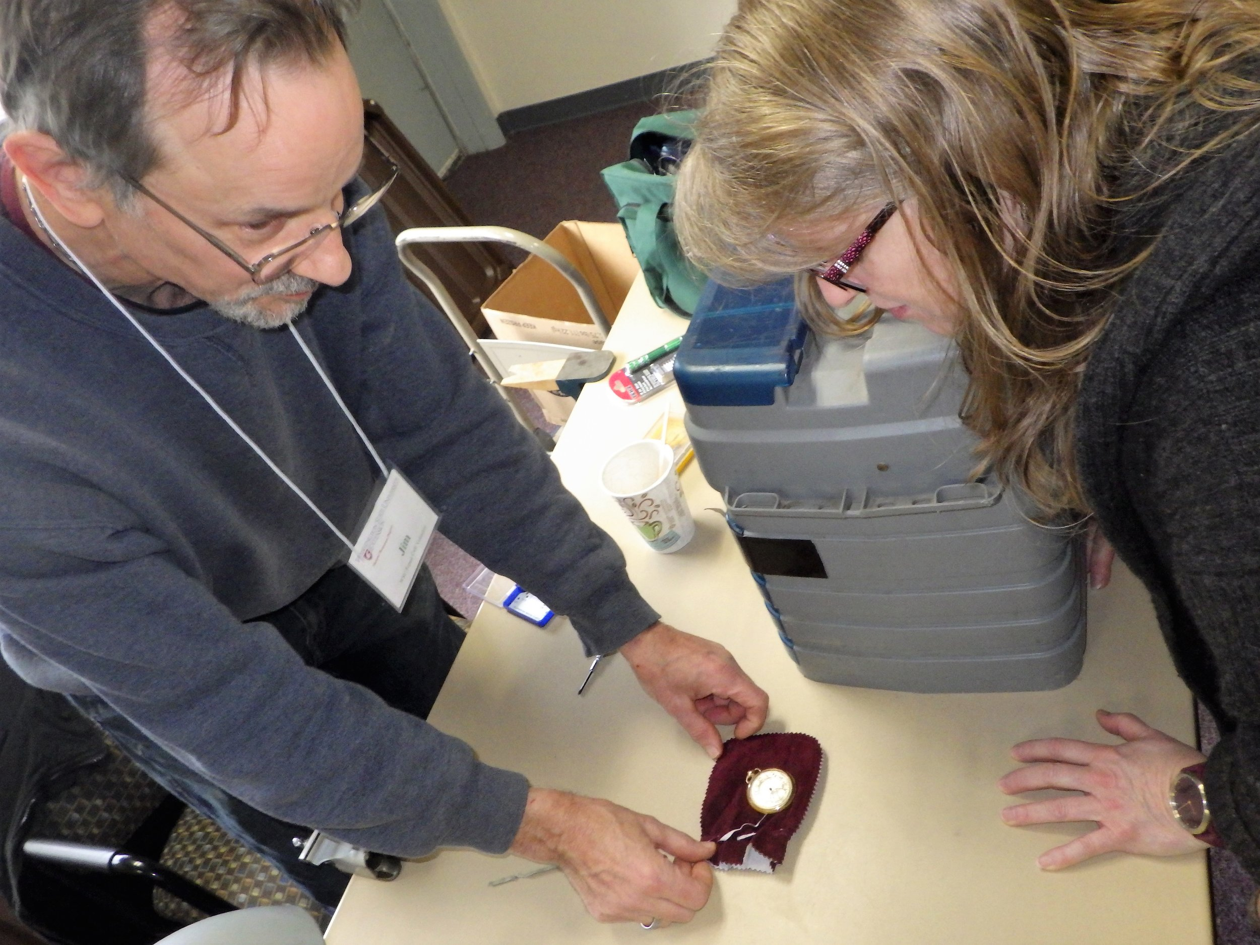 Repair Cafe volunteer Jim inspects a broken pocket watch // Kate Bobal
