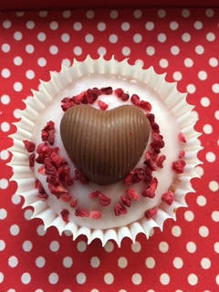 Raspberry and coconut cupcake with chocolate heart and freeze dried raspberries