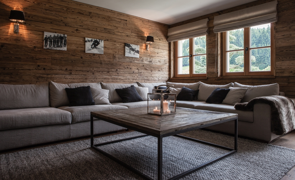 Natural wooden walls and floor in an cosy Austrian chalet. Carpet, handwoven lambswool - Table, simply forged raw iron with wooden plate - couch set-up, pure linen...