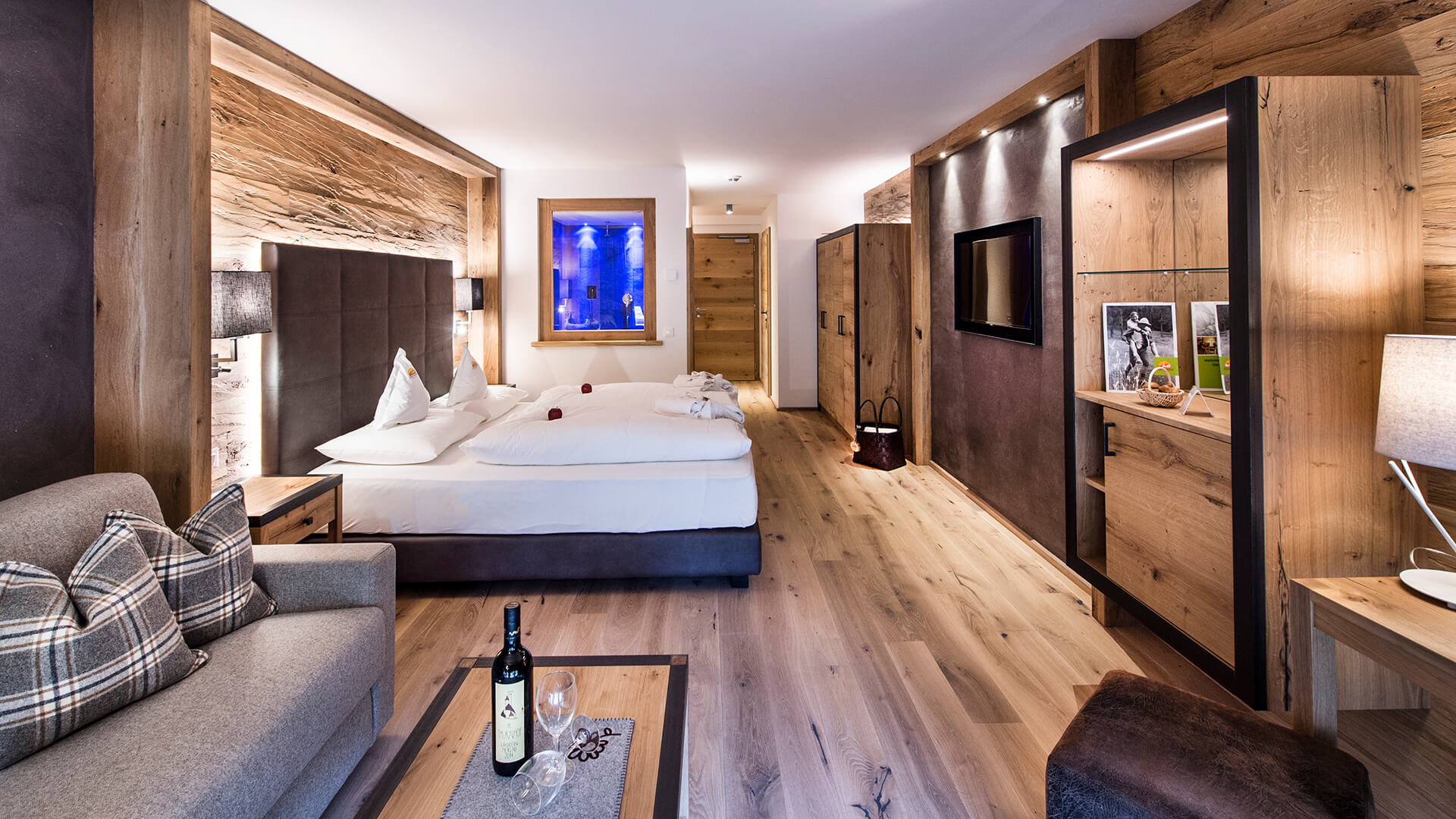 Hotel suite - oiled natural wooden floor, hacked oak walls,  oak wood cabinets. Lower bed coverage, large head board, stool and cinema panel covered with soft vegetable tanned buffalo leather. Couch, loden fabric...