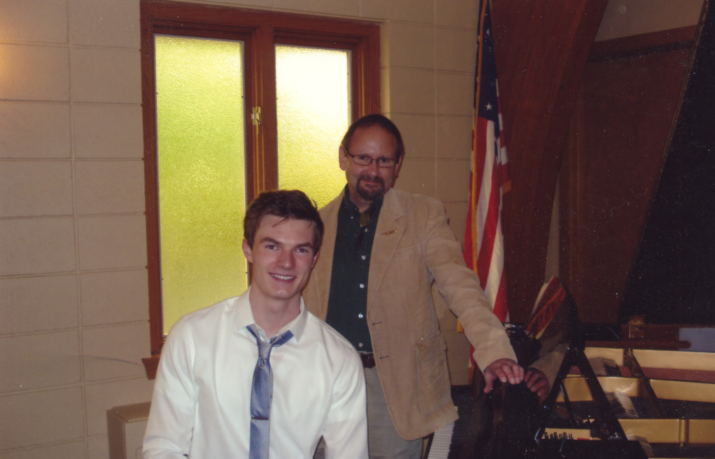 Bruce Clark at the piano with a student