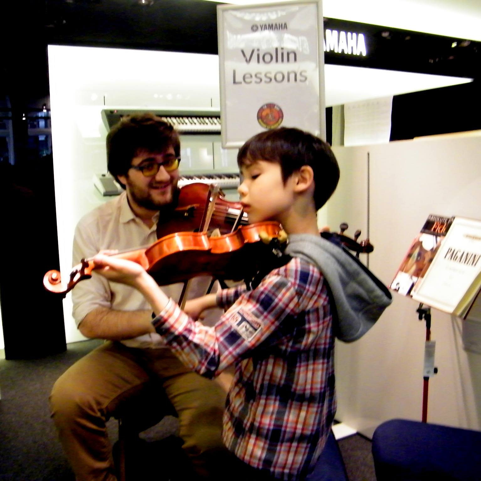 Elliot guides a first time Violin player through the basics during a Yamaha Music 'Learn to Play Day' in 2015.