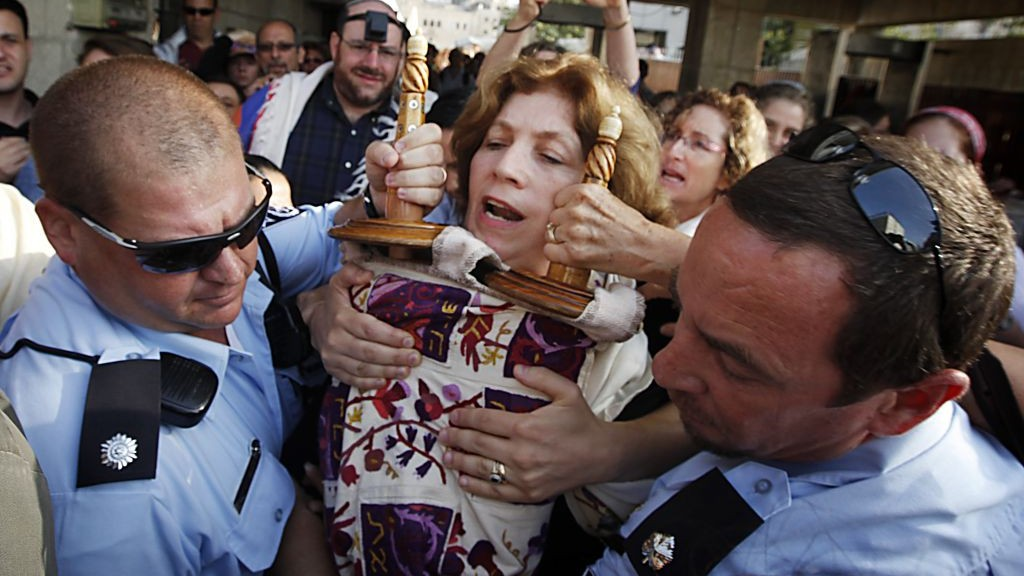 POLICE ESCORT ANAT HOFFMAN HOLDING A TORAH SCROLL FROM THE WESTERN WALL, ON JULY 12