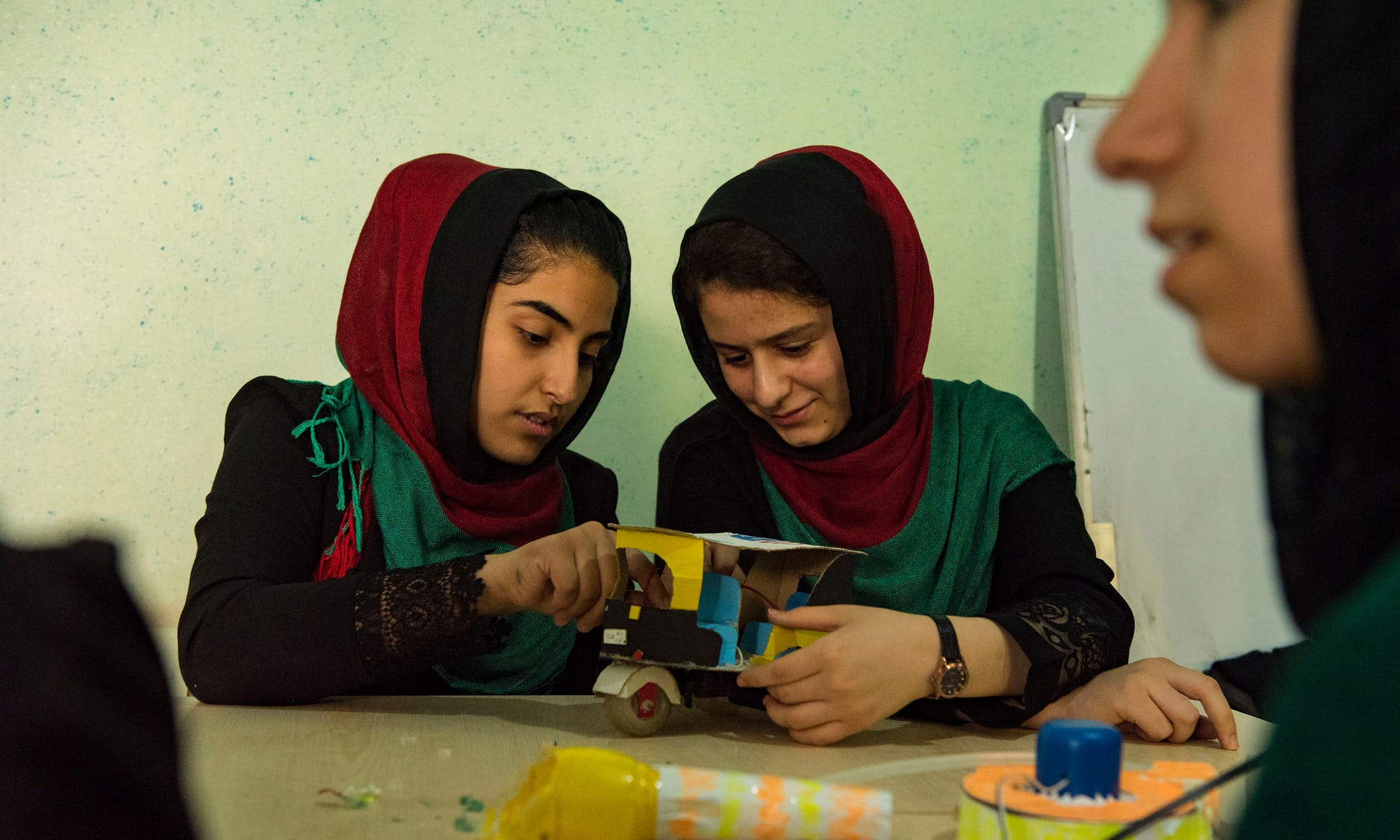 Lida Azizi (left) and Kawsar Roshan in Herat, building a self-driving miniature rickshaw decked with Afghan and American flags. Photograph: Sune Engel Rasmussen