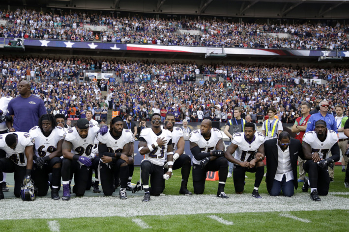 Baltimore Ravens players, including former player Ray Lewis, second from right, kneel down during the playing of the U.S. national anthem before an NFL football game against the Jacksonville Jaguars at Wembley Stadium in London on Sunday. Photo: Matt Dunham/AP