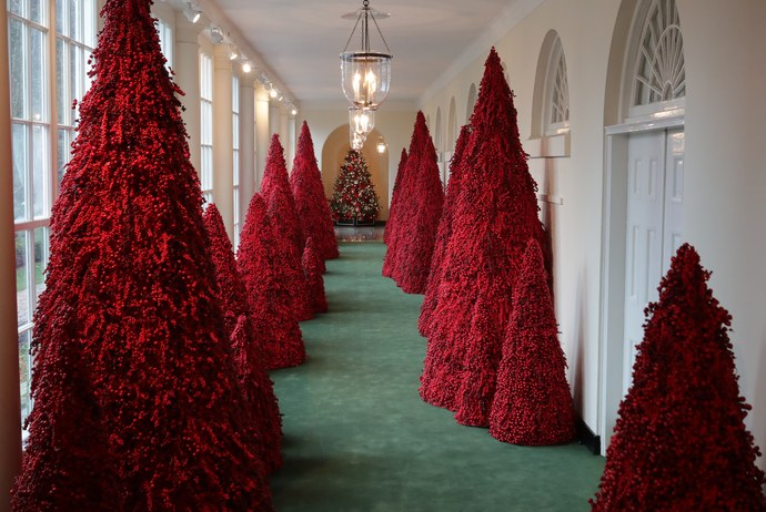 More than 40 red topiary trees line the East colonnade as part of the holiday decorations at the White House November 26, 2018.  By Chip Somodevilla/Getty Images.