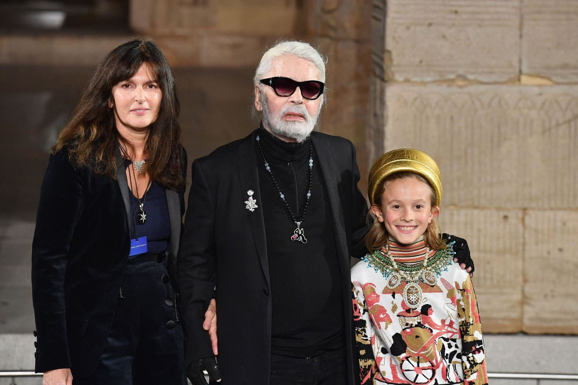 Karl Lagerfeld walks the runway with Virginie Viard and his godson Hudson Kroenig during the Chanel Métiers d'Art 2018 show at The Metropolitan Museum of Art in New York City. Image credit: Angela Weiss / AFP