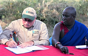 Azzedine Downes, IFAW President (left) and Mr. Daniel Leturesh, representing the Masai community, sign the Kitenden corridor certificates after they signed a lease agreement, 17 July 2013, in Amboseli National Park in Kenya. © IFAW/K. Prinsloo