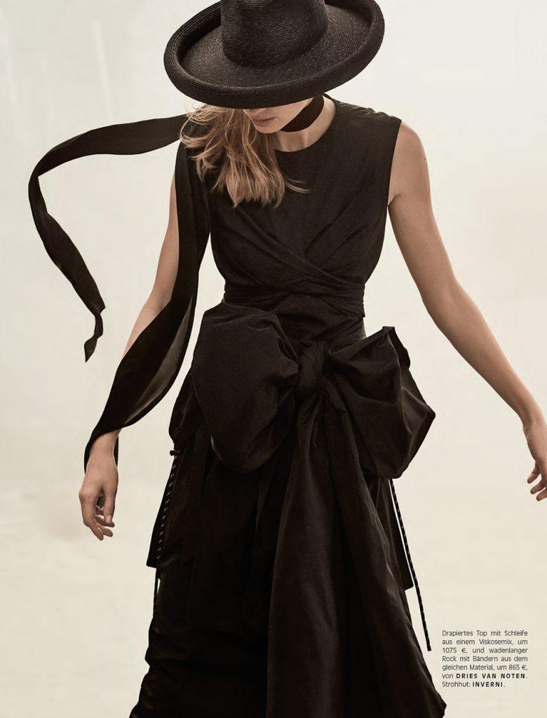 Julia Stegner wears black drama sobriety elegance with hats that match.