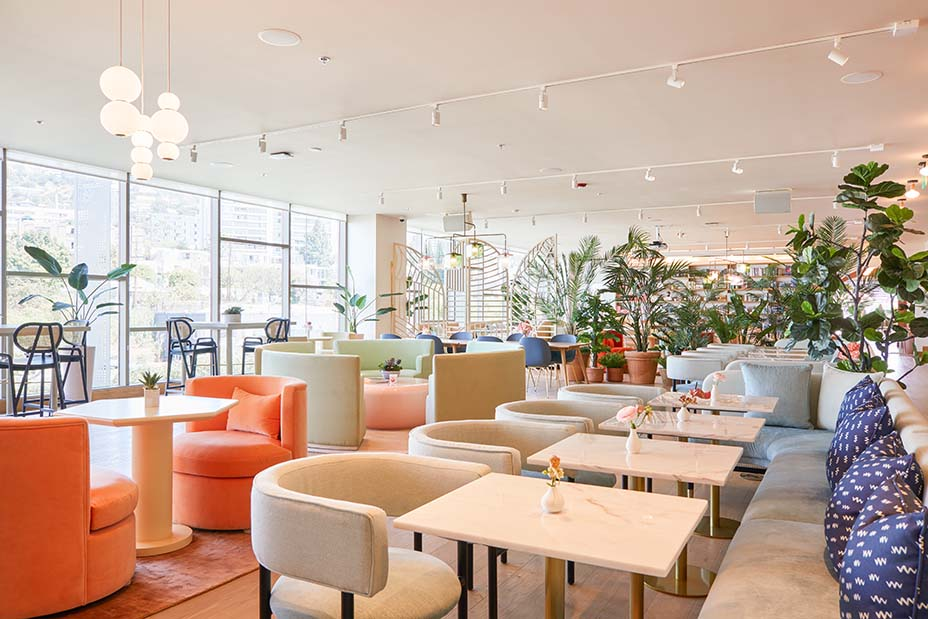 """The """"heart"""" of The Wing features custom-made individual and community working tables and chairs based on the height of women. Image Madeline Tolle/The Wing."""