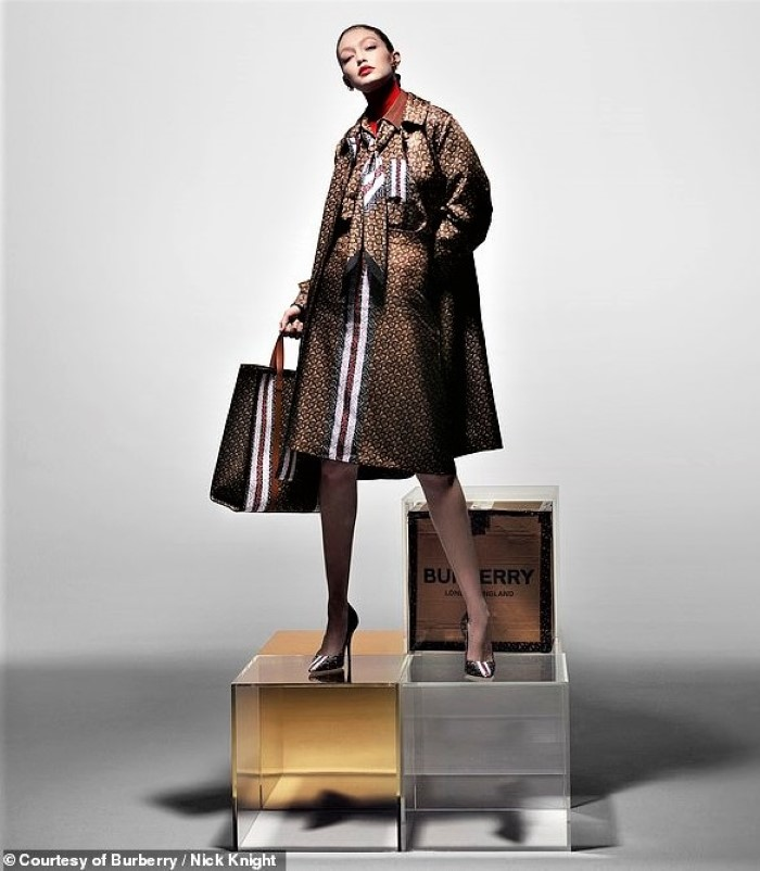 "As ""the Lady,"" Hadid is captured wearing the monogram Burberry trench and carrying a matching tote bag."