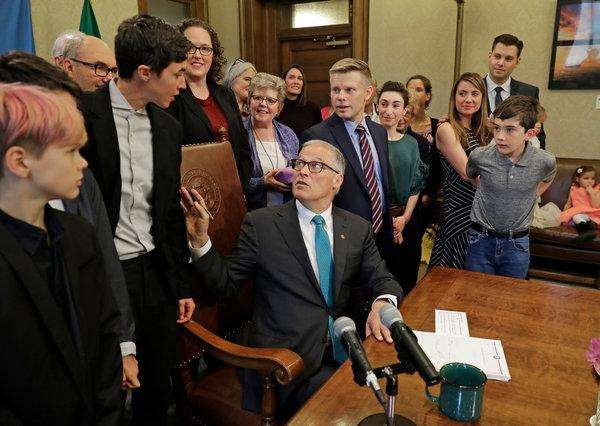 Washington State Governor Jay Inslee spoke to Katrina Spade, the founder of Recompose, as he signed a bill into law that allows licensed facilities to turn human remains into compost.  Image via  New York Times
