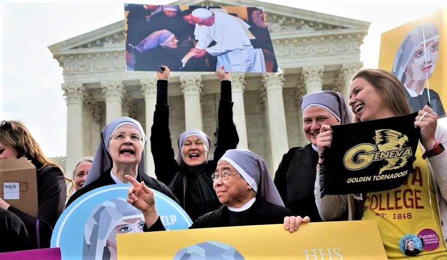 Photo by: Jacquelyn Martin. Nuns with the Little Sisters of The Poor, including Sister Celestine, left, and Sister Jeanne Veronique, center, rally outside the Supreme Court in Washington, Wednesday, March 23, 2016, as the court hears arguments to allow birth control in health care plans in the Zubik vs. Burwell case. (AP Photo/Jacquelyn Martin) ** FILE **