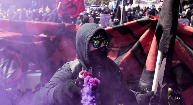"PROTESTERS IN BLACK, ASSOCIATED WITH ANTIFA, SHOWN AT A ""NO-TO-MARXISM"" RALLY AUG. 27 IN BERKELEY, CALIFORNIA. THE RALLY HAD BEEN CANCELED, BUT STILL ATTRACTED ATTENDEES AND DEMONSTRATORS TO MARTIN LUTHER KING, JR. CIVIC PARK ALONG WITH SCORE OF POLICE IN RIOT GEAR. 