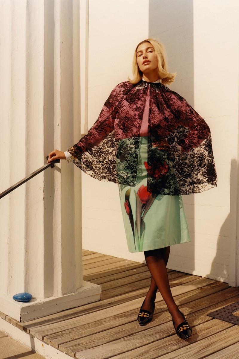 Prada cape, sweater, shirt, and skirt; Bottega Veneta bracelet and shoes; Wolford tights. Hailey Bieber by Colin Dodgson for W Magazine.