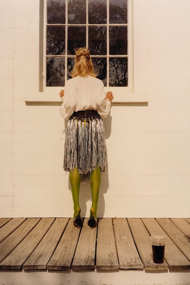 Loewe blouse and fringed belt; Bottega Veneta bracelet and shoes; Music Legs tights.