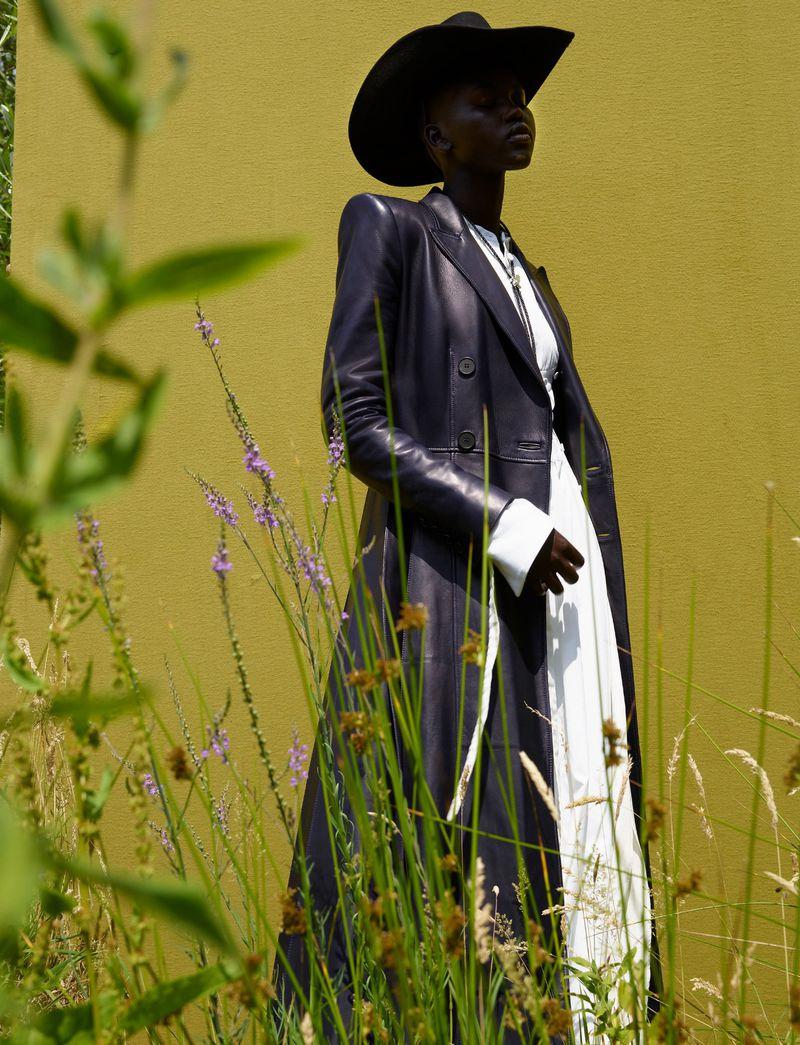 Leather knife pleat coat and pleated shirt dress Alexander McQueen, felt hat Jessie Western, bolotie Cenci. Adut Akech by Vivianne Sassen for Dazed Autumn 2019.