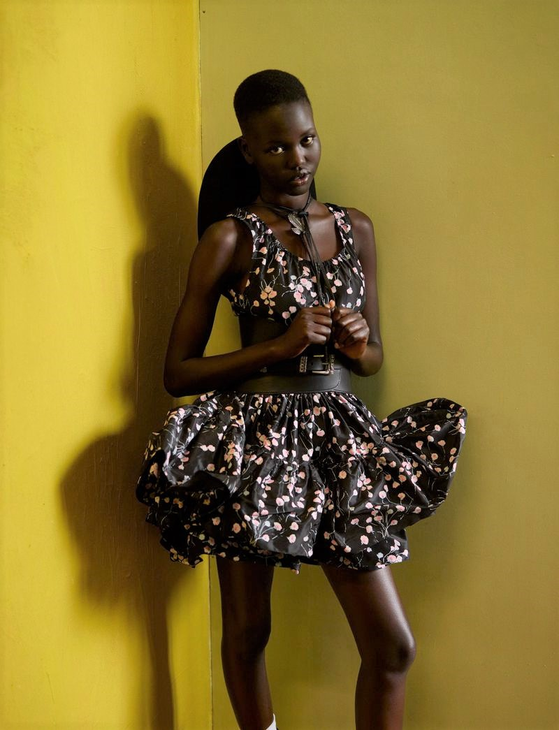 Silk floral print dress Miu Miu, felt hat Jessie Western, bolo tie Cenci, leather waist belt Etro, cottonsocks Calzedonia. Adut Akech by Vivianne Sassen for Dazed Autumn 2019.