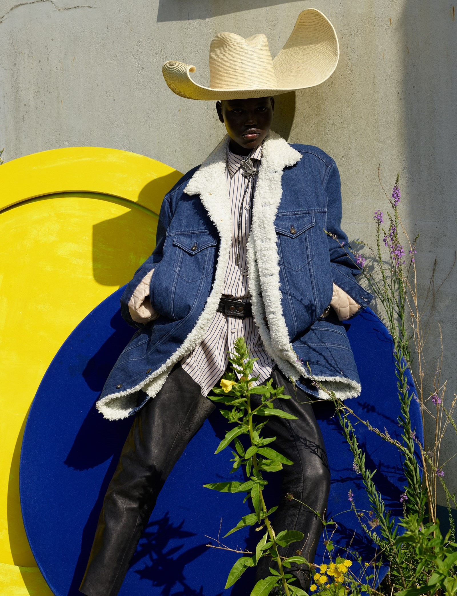 Shearling jacket Y/Project, striped cotton shirt Gucci, leather chaps Angharad Merrey for Savannah, warped palm leaf sombrero Melissa Eakin, leather bolo tie Cenci. Adut Akech by Vivianne Sassen for Dazed Autumn 2019.