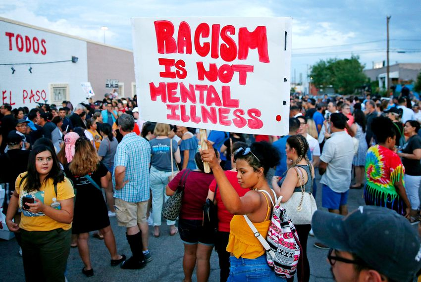 A woman holds a sign after a silent march to Las Americas Immigrant Advocacy Center for the victims of the Walmart shootings in El Paso August 4, 2019. Image via Michael Chow/The Republic via REUTERS