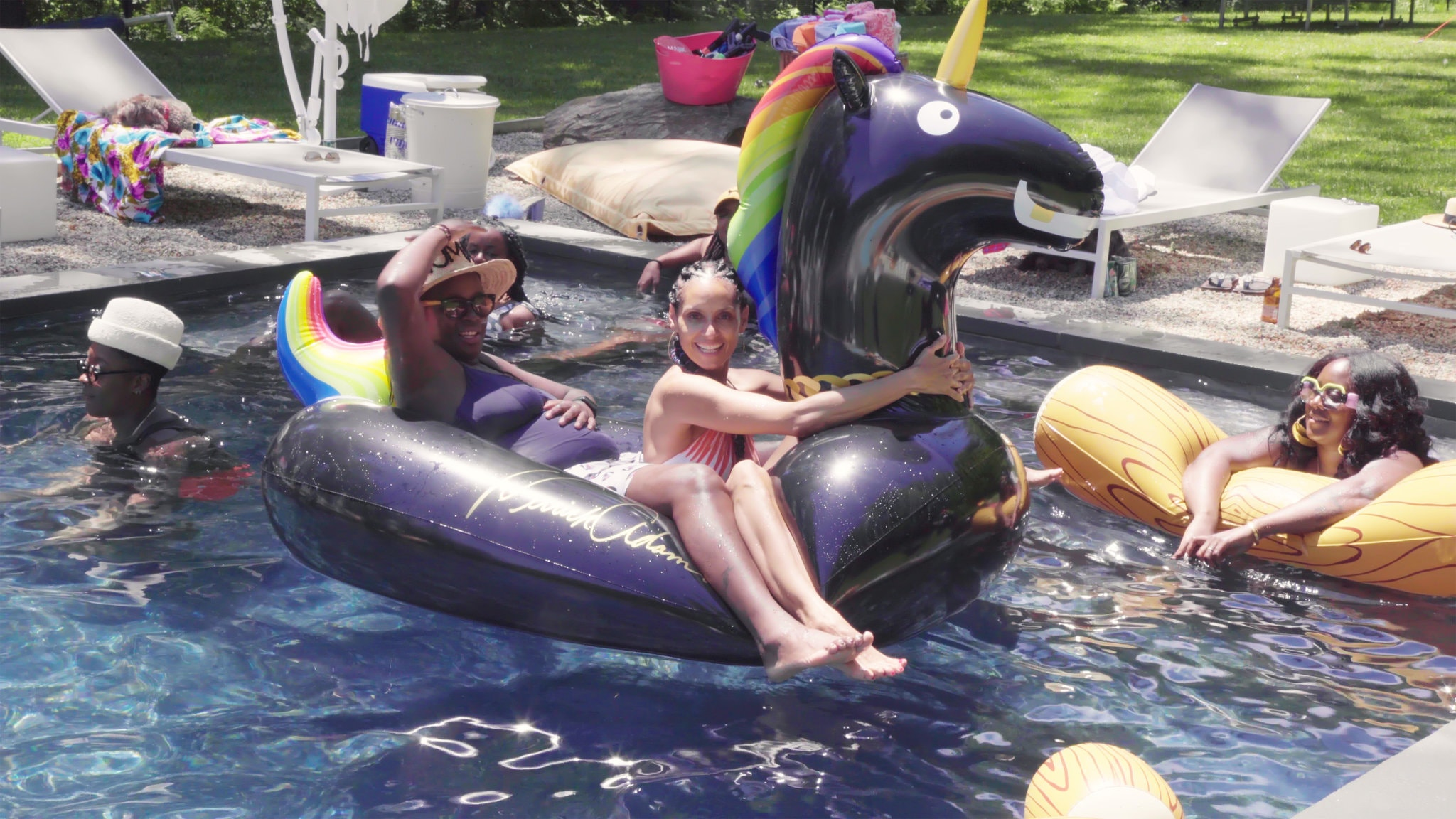 Thomas, left, and Chevremont in their swimming pool, seated on a float designed by the artist Derrick Adams.CreditScott J. Ross.