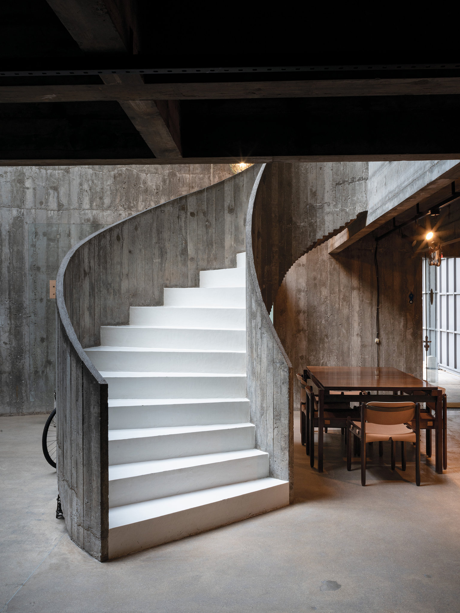 A wood-grain spiral concrete staircase that leads to the five bedrooms of Casa Millán, completed in Cidade Jardim in 1970 by the architect Paulo Mendes da Rocha. The table and chairs beneath it are 1960s-era designs by the Brazilian midcentury Modernist Jorge Zalszupin.CreditTodd Hido  via   New York Times