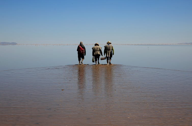 Poor countries have borne the brunt of global climate change. Here, indigenous Urus Muratos men walk on the dried-out Lake Poopo, once Bolivia's second-largest water body.  Reuters/David Mercado