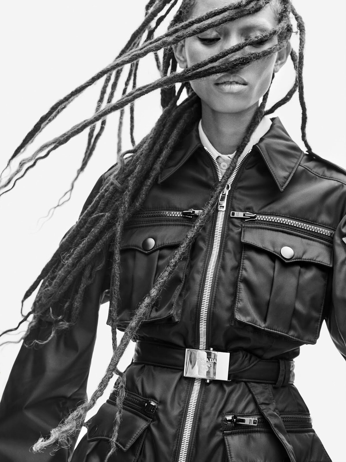 Miuccia Prada's waist-cinching belts temper her toughened-up utility pieces, creating a womanly silhouette in wear-forever cargo jackets.  Jacket, and shirt, both Prada.  Adesuqa Aighewi by Philip Messmann.